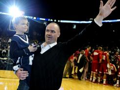 New Penn State football coach Bill O'Brien is announced to the crowd, with his 6-year-old son Michael, during a timeout at a Nittany Lions men's basketball game in January.