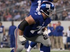 New York Giants quarterback Eli Manning calls out signals as Chris Snee listens during their game against the Dallas Cowboys on Dec. 11, 2011.