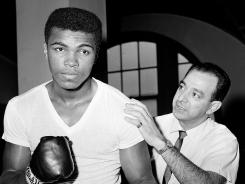 In this February 1962 photo, then-Cassius Clay (soon to be Muhammad Ali) works with longtime trainer Angelo Dundee. The two were most recently together for Ali's 70th birthday party on Jan. 17.