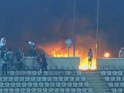 This image made from Egypt TV shows fans and a fire at a soccer stadium in Port Said, Egypt, Wednesday. Dozens of Egyptians were killed following a soccer match in Port Said when fans flooded the field seconds after the match. It was one of the worst incidents of sports violence in Egypt in decades.