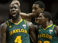 Baylor forwards Quincy Acy (4) and Perry Jones III and guard A.J. Walton (22) celebrate their victory on Wednesday night at Reed Arena.