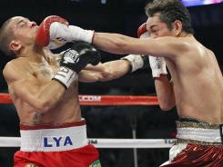 Wilfredo Vazquez, Jr., left, and Nonito Donaire exchange punches during the fifth round of their WBO junior featherweight title fight Saturday night. Donaire won by split decision.