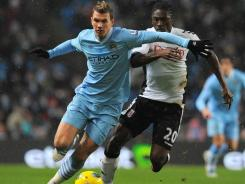 Manchester City striker Edin Dzeko, left, vies with Fulham midfielder Dickson Etuhu during the first half at the Eithad Stadium in Manchester.