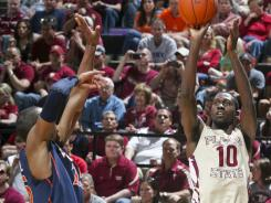 Florida State's Okaro White (10), shooting from the corner over Virginia's Akil Mitchell, finished with 13 points in the Seminoles' 58-55 win.