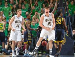 Fighting Irish forward Jack Cooley (45) and guard Scott Martin (14) celebrate after an Irish basket in the first half against Marquette on Saturday.