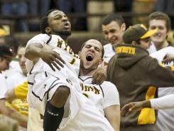Wyoming Cowboys guard JayDee Luster (1) is lifted up by teammate Arthur Bouedo (behind) as they celebrate a victory over the UNLV Rebels at the Arena Auditorium. The Cowboys defeated the Rebels 68-66.