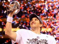 New York Giants quarterback Eli Manning hoists the Vince Lombardi Trophy after defeating the New England Patriots 21-17 in Super Bowl XLVI.