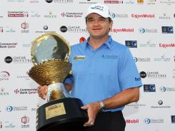Paul Lawrie of Scotland holds his trophy after winning the Qatar Masters at the Doha Golf Club on Sunday.