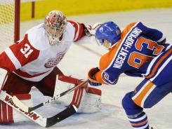 The Oilers' Ryan Nugent-Hopkins, right, scores the winning shootout goal on Red Wings goalie Joey MacDonald on Saturday.