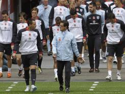 England's manager Fabio Capello (center) talks to John Terry as he leads his team out onto the pitch for a training session at Wembley Stadium in London on Nov. 11, 2011.