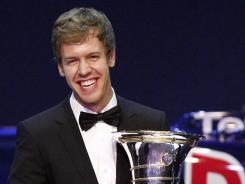 Formula One driver Sebastian Vettel poses with his FIA trophy to celebrate his dominant 2011 championship in New Delhi.