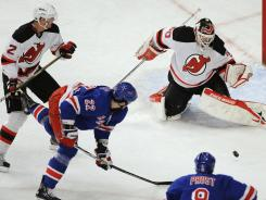 Devils goalie Martin Brodeur protects the net with help from defensman Mark Fraser. Brodeur was perfect on this night, stopping all 30 Ranger shots for his ninth career shutout against New York.