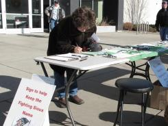 A woman signs petitions supporting the University of North Dakota nickname, the Fighting Sioux, on Tuesday.