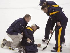 Buffalo Sabres coach Lindy Ruff is helped on the ice after being injured during practice Monday. He suffered three broken ribs.