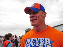 Pro wrestler John Cena, shown walking through the garage at a 2010 race at Pocono Raceway, accepted the job of honorary starter at the Daytona 500 from Carl Edwards.