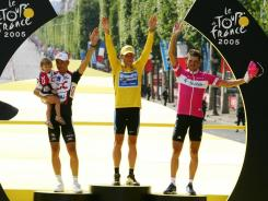 A file photo taken on July 24, 2005 shows, from left, Italian Ivan Basso, carrying his child, overall winner Lance Armstrong of the United States and German Jan Ullrich celebrating on the podium after the 21st stage of the 92nd Tour de France.