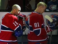 Montreal centers Scott Gomez (11) and Lars Eller (81) stand for the national anthem prior to the Canadiens' game against the Winnipeg Jets on Feb. 5.