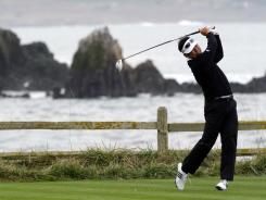 Charlie Wi hits off the 18th tee of the Pebble Beach Golf Links during the second round of the AT&T Pebble Beach National Pro-Am golf tournament in Pebble Beach, Calif. Wi sits atop the leaderboard with a 3-stroke lead.