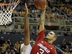 Louisville's Peyton Siva goes up for a basket over West Virginia's Kevin Jones.