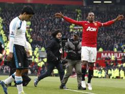 Manchester United's Patrice Evra, right, celebrates as Liverpool's Luis Suarez dejectedly wals off the field after Manchester United's 2-1 Saturday.