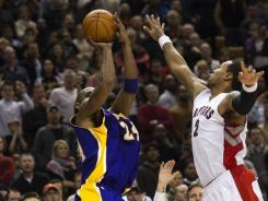 Lakers guard Kobe Bryant makes the game-winning jump shot over Raptors forward James Johnson on Sunday.