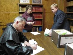 Minot attorney Reed Soderstrom, left, chairman of a referendum campaign to require the University of North Dakota to use its Fighting Sioux nickname, signs some petition paperwork. State elections director Lee Ann Oliver, center, and deputy secretary of state Jim Silrum, right, work to sort the petitions.