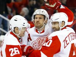 Red Wings defenseman Niklas Kronwall (center) receives congratulations from left wing Jiri Hudler and center Henrik Zetterberg after scoring in the first period.