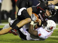 Ball State linebacker Travis Freeman, bottom, sacks Northern Illinois quarterback Chandler Harnish during a game last season.