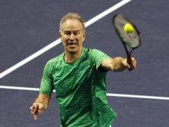 John McEnroe hits an overhead smash during an exhibition doubles victory Monday at the SAP Open in San Jose.