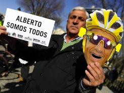 "A fan of Spanish cyclist Alberto Contador holds a placards reading ""We are all Contador"" during a symbolic bike ride on Sunday in Pinto, Contador's home town, to support him over his two-year doping ban."