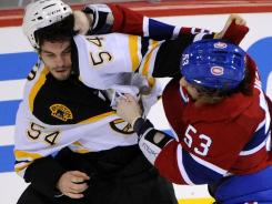 Boston defenseman Adam McQuaid (54) and Montreal forward Ryan White fight during the first period at the Bell Centre.