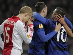 Denmark's Nicolai Boilesen of Ajax grabs his head as Manchester United players, including No. 10 Wayne Rooney, celebrate scoring a goal during a Europa League soccer match in Amsterdam.