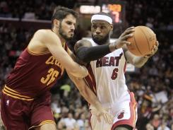 Miami's LeBron James (6) drives to the basket against Cleveland's Omri Casspi (36). The Heat won 111-87. James scored 28 to lead his team to their fifth straight victory.