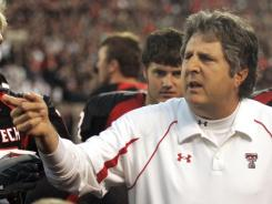 Then-Texas Tech football coach Mike Leach talks with his team in 2009.