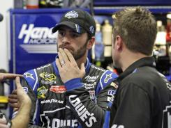 Jimmie Johnson, left, meets with crewmembers after parts of the No. 48 Chevrolet were taken by NASCAR on Friday.