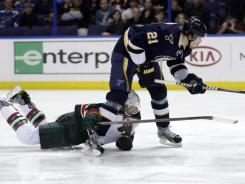 The Wild's Greg Zanon trips up the Blues' Patrik Berglund (21) while on a a breakaway, drawing a penalty shot, in the second period. Berglund missed his penalty shot high with a backhand.