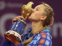 Victoria Azarenka kisses the trophy after beating Samantha Stosur of Australia in the Qatar Open final.