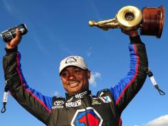 NHRA Top Fuel dragster driver Antron Brown celebrates after winning the Arizona Nationals at Firebird International Raceway.