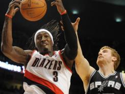 Portland Trail Blazers forward Gerald Wallace (3) grabs a rebound in front of San Antonio Spurs forward Matt Bonner (15) during the first quarter at the Rose Garden.