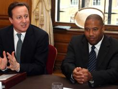 British Prime Minister David Cameron (left) sits next to former soccer player John Barnes at a roundtable discussion about racism and discrimination with former players and bosses at Downing Street in central London on Wednesday.