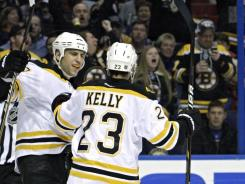 Boston Bruins' Chris Kelly (23) celebrates with teammate Milan Lucic after scoring a goal in the first period in St. Louis.