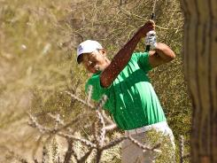 Tiger Woods plays his second shot from the desert on the 10th hole during the first round of the WGC-Accenture Match Play Championship.