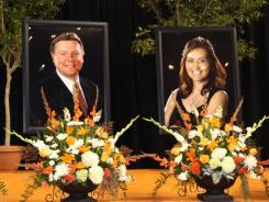 Flowers stand in front of portraits of Oklahoma State women's basketball coach Kurt Budke, left, and assistant coach Miranda Serna during a memorial gathering in November.