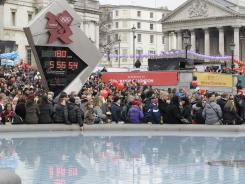 In this Jan. 29, 2012 file photo, people gather around the Olympic countdown clock at Trafalgar Square in London to watch the Chinese New Year celebration. Trafalgar Square will host a giant video screen free to the public, showing events from the London 2012 Olympics.