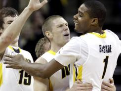 Iowa's Melsahn Basabe (1) celebrates with teammates Matt Gatens, center, and Zach McCabe after upsetting No. 15 Wisconsin.