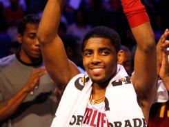Kyrie Irving lifts the MVP award during the BBVA Rising Stars Challenge in Orlando.