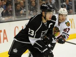 Blackhawks right wing Michael Frolik (67) pursues Kings right wing Dustin Brown (23) as the latter chases down the puck. The Kings won 4-0 behind Brown's three goals, which all came in a span of 15 minutes.