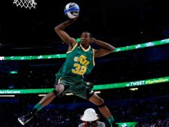 Sporting the jersey of Jazz legend Karl Malone, Jeremy Evans leaps over comedian Kevin Hart on his way to winning the Slam Dunk Contest.