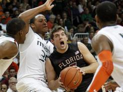Seminoles guard Luke Loucks is met by a swarm of Hurricanes as he drives to the basket during their Sunday matchup. Miami upset Florida State thanks to Durand Scott's 17 points.