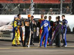 Drivers gather on the backstretch during the red-flagged Daytona 500 late Monday night.